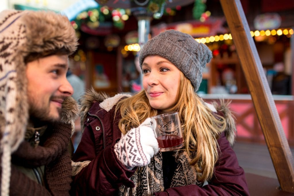 Paar Frau Mann hat Spa auf dem Weihnachtsmarkt sieht sich verliebt an und lacht