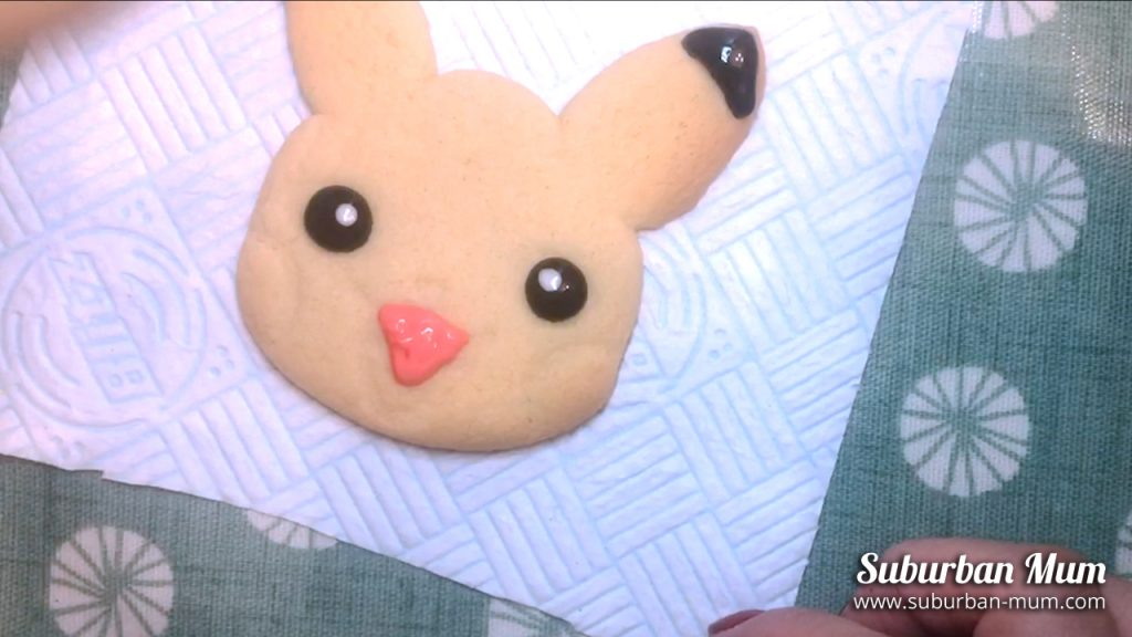 using pink icing to ice the tongue on the pikachu cookie