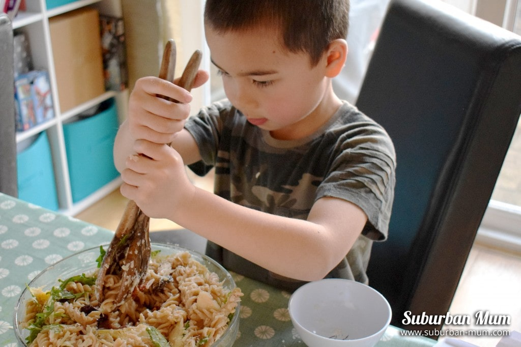 M mixing pasta salad