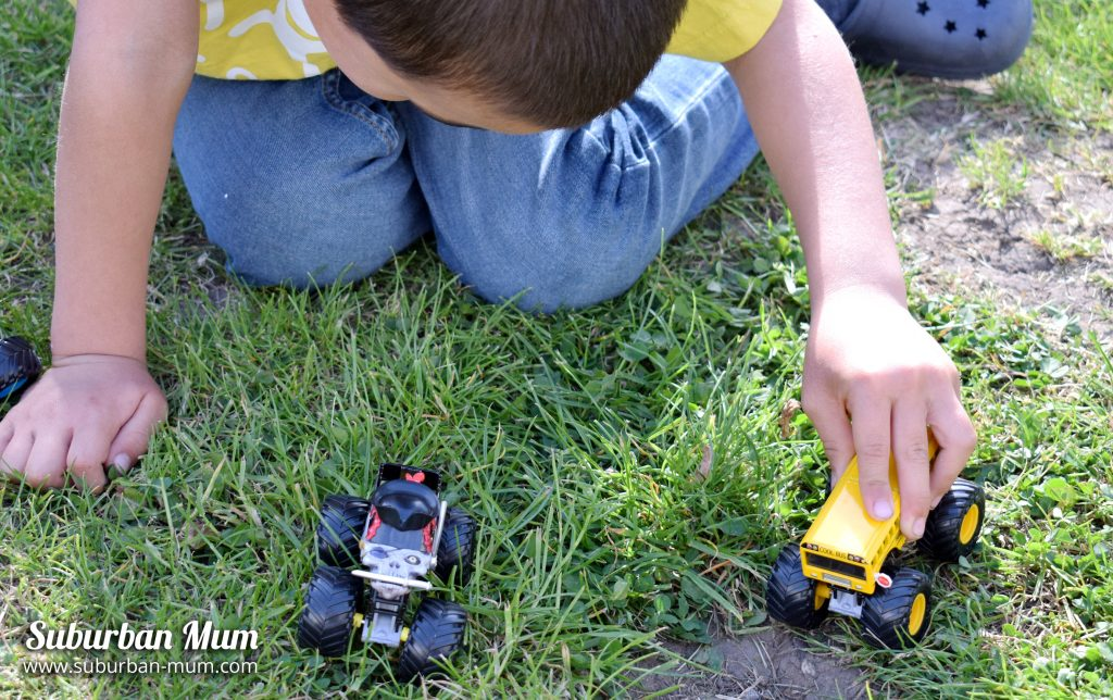M playing with Monster Jam Monster Truck die-cast vehicles