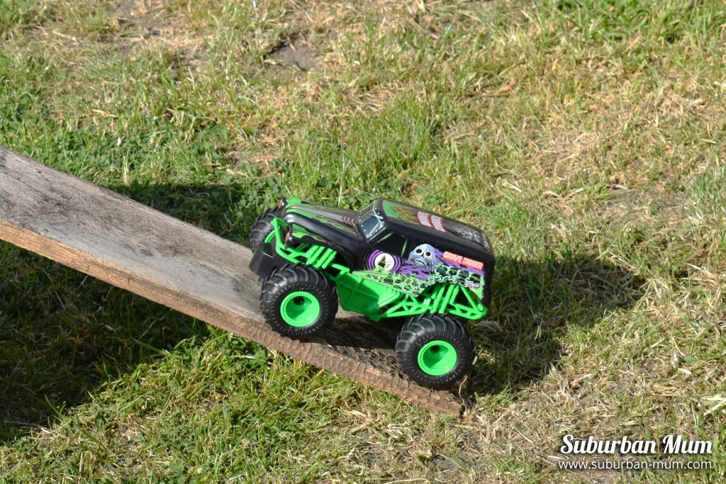 Monster Jam Grave Digger remote control car going up a ramp in the garden