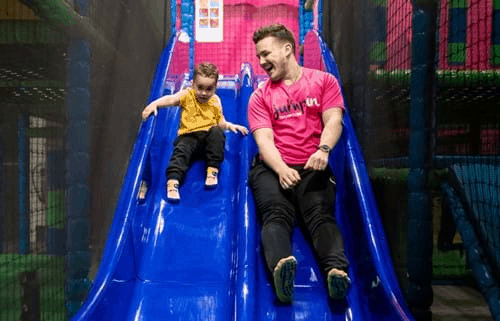 Jump In staff member sliding down a slide with a young child